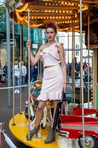 Guess met een roze jurk op de draaimolen