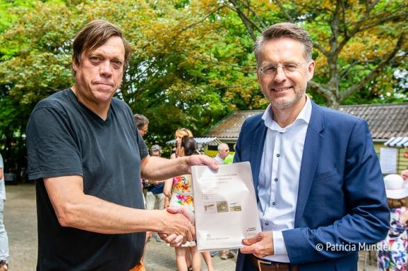 Hendrik Baas overhandigt een onderzoeksrapport over het Westerpark aan Robin Paalvast